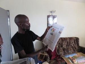 John Kamicha showing newspaper